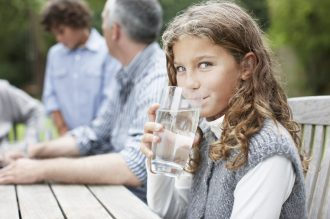 Girl drinking water at picnic table