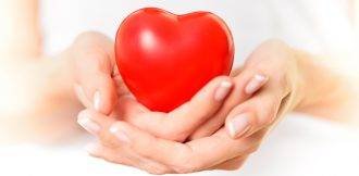 A woman wearing white top holding a heart in cupped hands. Picture with very thin deph of field.
